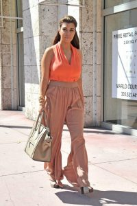 Kourtney Kardashian goes pretty in pink and orange, wearing peach pants, a tight orange top and a matching bag, as she shops for a new Dash store with her assistant in Miami